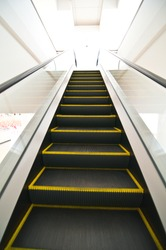 Escalator with yellow strips and glassy stair railing leading downstairs. Portrait orientation