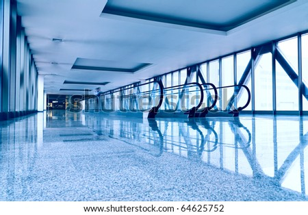 Escalators in modern business center. Tint blue