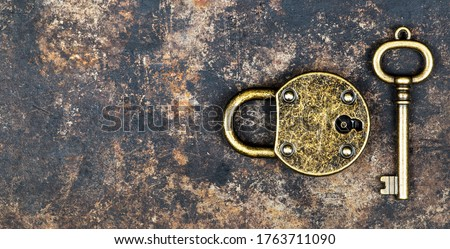 Escape room game concept. Web banner of a vintage gold key and locked padlock on a rusty metal background.  Stock photo ©