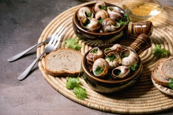 Escargots de Bourgogne - Snails with herbs butter, gourmet dish, in two traditional ceramic pans with coriander, bread and glass of white wine on straw napkin over brown textured background.