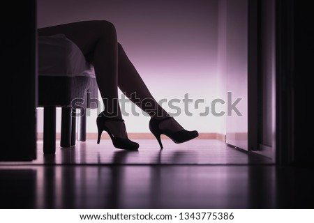 Escort, prostitute or sugar babe lying on bed with long legs and sexy high heels. Prostitution, sex work or sugar dating concept. Stripper or paid woman. Erotic body in bedroom.