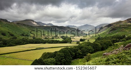 Eskdale valley in the English Lake District National Park with moody grey skies touching the mountain tops on the horizon. Green fields and trees in the foreground. #152365607