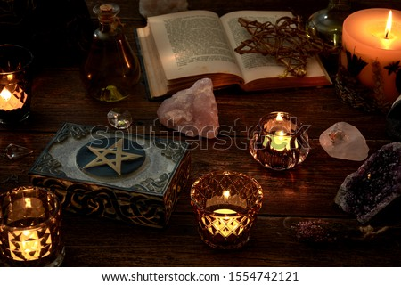 Esoteric or mystical still life with a box and a few burning candles, a pentagram next to an open book. Pendulum and precious stones on old wooden table top.