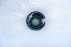Espionage background. Hidden camera lens in the snow. Black lens of the secret camera is hidden in the snow. Copy space