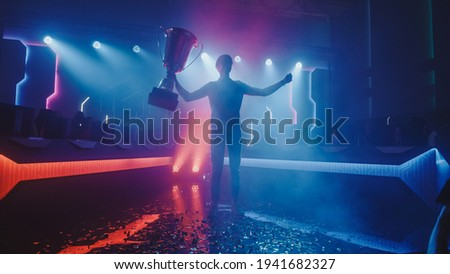 eSports Winner Trophy Standing on a Stage in the Middle of the Computer Video Games Championship Arena. Two Rows of PC for Competing Teams. Stylish Neon Lights with Cool Area Design. Photo stock ©