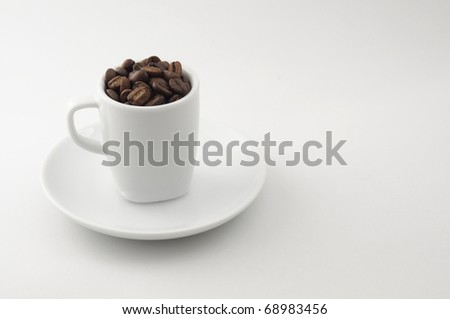 Espresso Coffee Beans. An espresso cup filled with coffee beans sits on a saucer. Photographed against neutral background.