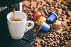 Espresso coffee capsules and machine maker on a wooden table, blur coffee pods and beans background