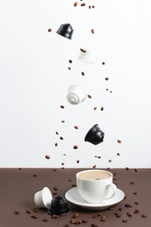 Espresso coffee capsules and roasted coffee beans levitating above coffee cup. Cappuccino made from coffee and milk capsules.