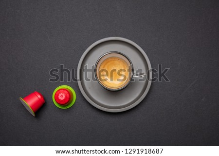 Espresso coffee cup and red compostable capsules, pods, on black color background, top view Сток-фото ©