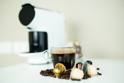 Espresso coffee in a cup surrounding with medium dark roasted coffee beans and coffee capsule close up with copy space.