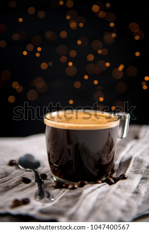 Espresso coffee in a glass cup surrounded by coffee beans and teaspoon on a gray cloth, and blurred lights in the dark background. #1047400567