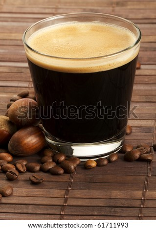 espresso coffee in a short glass with hazelnuts and coffee beans on wooden background