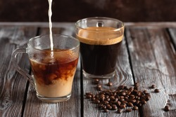 Espresso coffee in a transparent glass. Pour milk into coffee. Wooden dark rustic table. Selective focus