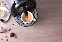 Espresso coffee machine with capsules and coffee served background on wood table. Top view