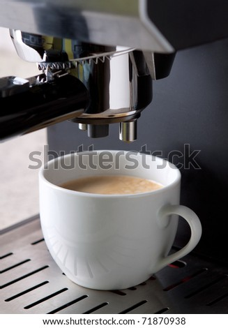 Espresso coffee maker in action with white cup