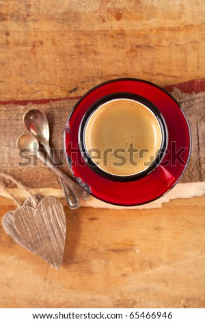 espresso coffee, red enamel mug, two old silver spoons, two wooden hearts, shallow dof