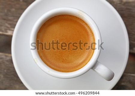 Shutterstock Espresso coffee shot brown crema froth in porcelain white cup with saucer over wooden table, detail close up, elevated top view