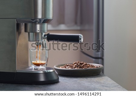 Espresso coffee trickles out of the home coffee machine and fills a beautiful transparent mug with two contours on the background of a Cup of coffee beans. Household coffee makers. #1496114291
