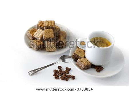 Espresso coffee with cookies and roasted coffee beans over white background.