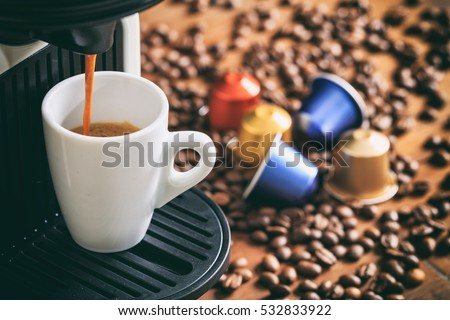 Espresso cooffe capsules and machine maker on a wooden table, blur coffee pods and beans background #532833922