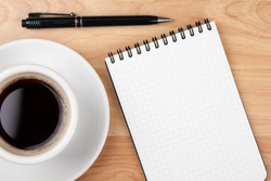 Espresso cup with blank notepad and pen on wood table