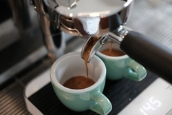 Espresso extraction by professional espresso machine at coffee shop. Espresso pour into the green cup on the scales.