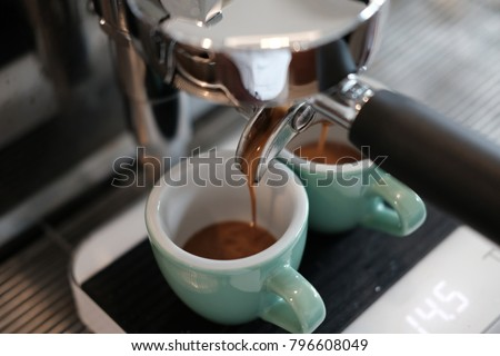 Espresso extraction by professional espresso machine at coffee shop. Espresso pour into the green cup on the scales. #796608049