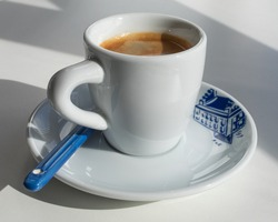 Espresso in a white cup with a blue print in the morning with shadows from the window
