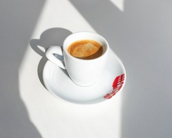 Espresso in a white cup with a red print in the morning with shadows from the window