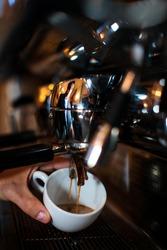Espresso is being prepared in coffee machine.
