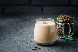 Espresso maca banana smoothie and coffee beans in glass jar on dark concrete background. Selective focus, space for text.