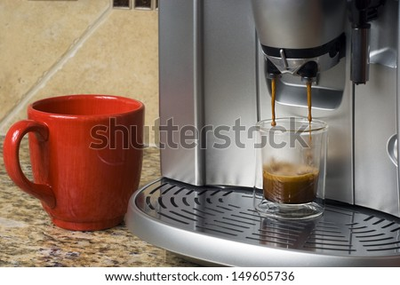 Espresso machine pouring shot into shot glass with red mug standing by.