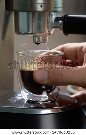 Espresso oozes out of home coffee and fills a beautiful transparent mug with two contours on the background of c serves coffee beans. Consumer electronics for the kitchen. #1498660235