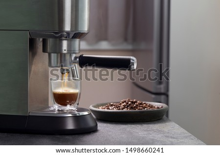 Espresso oozes out of home coffee and fills a beautiful transparent mug with two contours on the background of c serves coffee beans. Consumer electronics for the kitchen. #1498660241