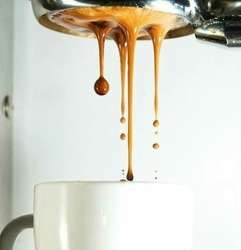 Espresso pouring from coffee machine into coffee cups