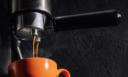 Espresso pouring from coffee machine into orange cup, close up.