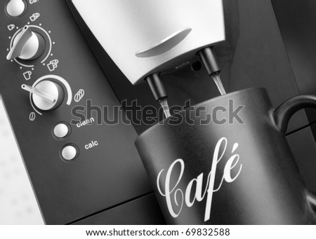 Espresso pouring into black cup from coffee machine