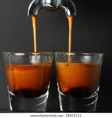 Espresso pouring into two shot glasses