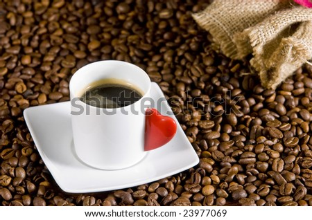 Espresso served on heart shaped cup on coffee beans