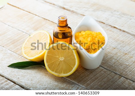 Essential aroma oil and sea salt with lemon on wooden background. Selective focus.