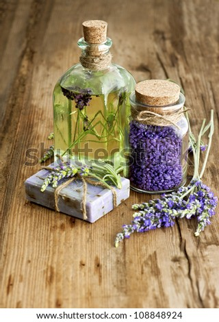 essential lavender oil, herbal soap and bath salt with fresh flowers on wooden background. selective focus - stock photo