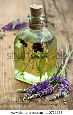 essential lavender oil with fresh flowers on wooden background. selective focus