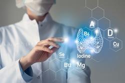 Essential nutrients for Thyroid Gland health including Iodine, Selenuim, Vitamin B6, Cuprum. Blurred portrait of doctor holding highlighted blue Thyroid Gland.