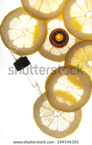 Essential oil amber glass bottle with dropper and some slices of lemon