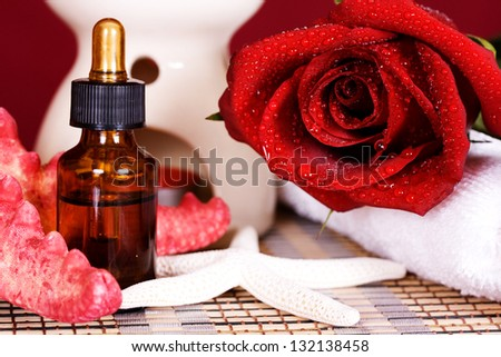 Essential oil and red rose a burning candle