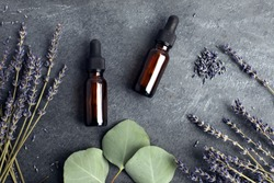 essential oil bottles on textured dark gray slate with lavender and eucalyptus for wellness spa, apothecary, homeopathic and natural health