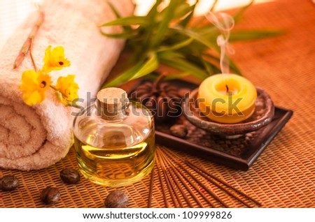 Essential oil bottles, towels, candle and flower in health spa for spa treatment. [Focus at the oil bottle]