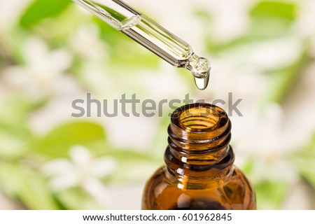 essential oil falling from glass dropper