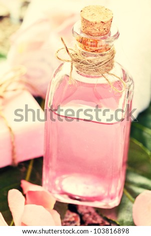 Essential Oil for Aromatherapy, with rose petals and soap - stock photo
