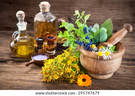 Essential oil, mortar with fresh herbs and bath salt on wooden background